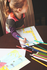 Little girl drawing a colorful pictures of giraffe and playing children using pencil crayons sitting at table