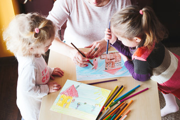 Mom with little girls drawing a colorful pictures using pencil crayons standing
