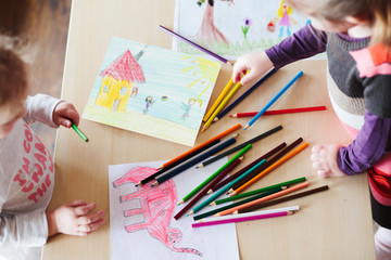 Little girls drawing a colorful pictures of elephant and playing children using pencil crayons standing at table. Shot from above