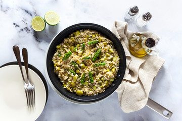 risotto with asparagus in a frying pan on a white marble table. shot from above. vegan and vegetarian healthy Italian cuisine.
