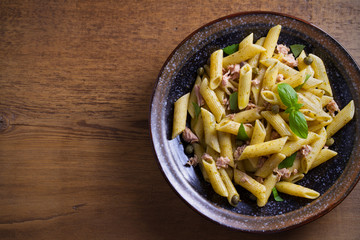 Tuna, basil and caper penne with pesto sauce in bowl on wooden background. Pasta with tuna fish. overhead, horizontal