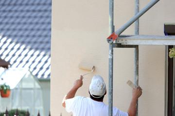 Malowanie wałkiem elewacji budynku.