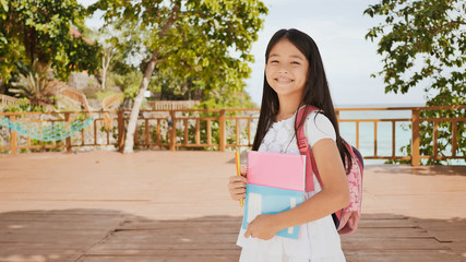 A charming philippine schoolgirl with a backpack and books in a park off the coast. A girl joyfully poses, raising her hands up with textbooks in her hands. Warm sunny day.
