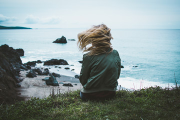girl sitting on a cliff overlooking the ocean with her hair blowing in the wind