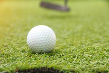 Golf ball putt on green grass targeted hole