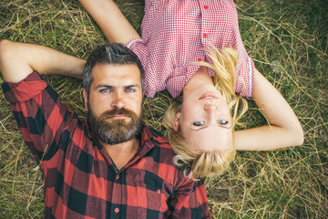 Couple in love lying on grass in forest or park. Romantic date in nature, love and relationship concept. Bearded man with blue eyes and beautiful blond girl in retro dress enjoying summer evening