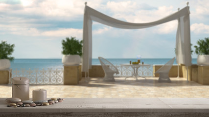 Wooden vintage table top or shelf with candles and pebbles, zen mood, over blurred empty classic terrace with sea panorama, white architecture interior design