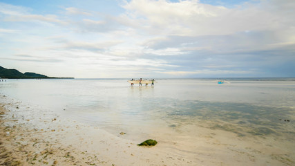 Fishermen carry a boat to the sea. Bohol Island. Philippines.
