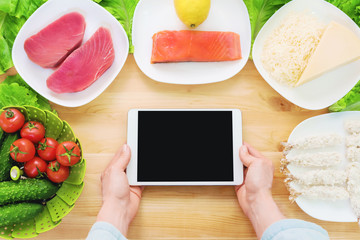 Close-up top view of female hands holding a tablet computer with a blank display surrounded by healthy food on a home kitchen table. Workpiece to insert the design of the mobile application into the
