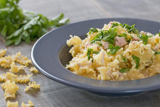 A plate with mafalda pasta with tuna and parsley.
