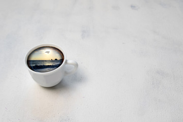 Ocean or sea in cup.Cup of coffee with the sea inside on white vintage table.