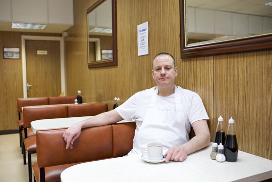 Portrait of chef sitting at table in diner