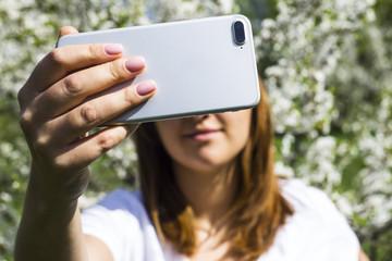 The girl makes selfie opposite the spring white flowering tree. Spring time concept
