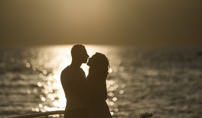 Silhouette of sensual couple kissing with sunset above sea surface on background. Couple in love on romantic date in evening at seafront, defocused, copy space. Romance and love concept.