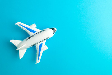 Close-up white plane toy on blue background.  Concept of traveling