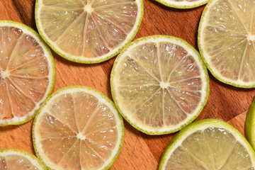 Fresh and bright sliced lime on a wooden surface