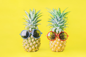 Pineapples with red and blue sunglasses on yellow background - Summer background