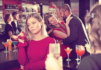 Girl upset because boyfriend flirting with other woman in bar