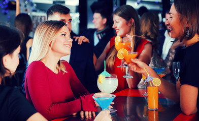 Woman with colleagues on corporate party in bar