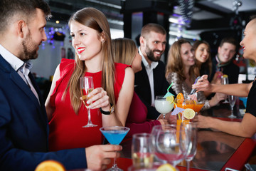 Woman and her boyfriend with cocktails having fun at nightclub