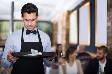 disgruntled waiter holding serving tray with tips