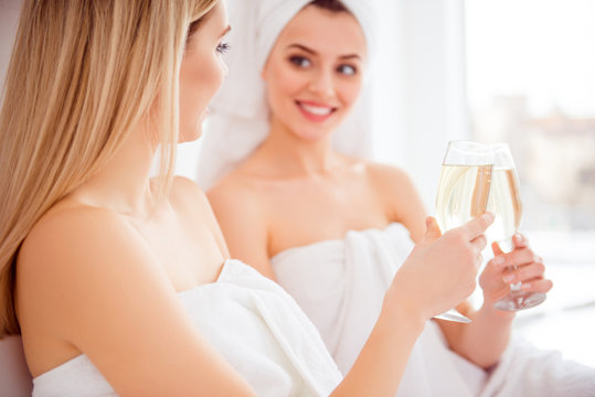 Cropped close up portrait of joyful, cheerful models after shower, bath having glasses with sparkling wine in hands, clinking, celebrating holiday, event, having fun, enjoying gathering meeting