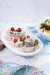 Holiday dinner. Food of Holland. Sandwiches with herring on a white plate. Free space for text