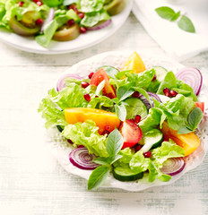 Red and yellow fresh tomato salad with  pomegranate seeds