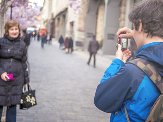 teenager son making a photo of his adult mother in the city streets