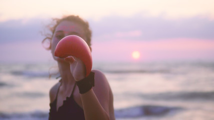 Karate sport girls exercise, training karate on ocean beach against sunset, focus to gloves