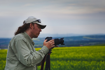 Photographer is setting up camera on a tripod in nature