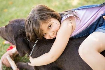 Innocent little girl hugging pet dog