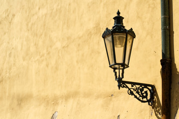 Street lamp on the orange wall. Black metal street historic lamp on an old yellow orange wall.