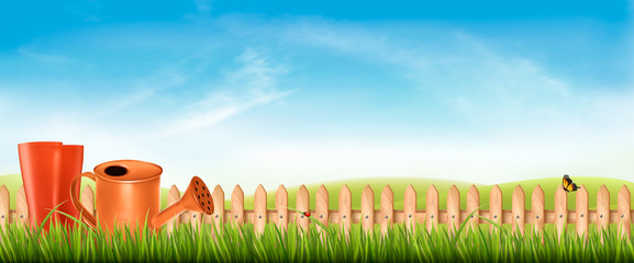 Wall Mural - Rubber boots with watering can in a green grass on garden background. Vector