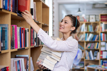 Young woman with a stack of books in library Wall mural