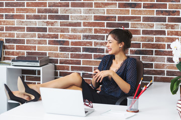 Excited laughing business woman sitting in a modern office