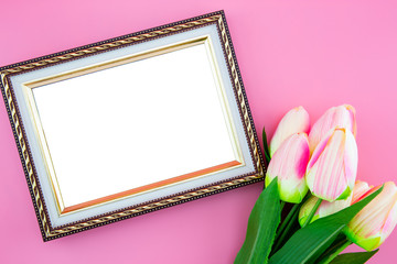 Beautiful of yellow tulip flower and photo frame border, with flat lay on the pink background, top view, copy space, mother day and holiday concept.