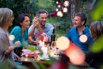 Group of friends gathered around a table in a garden on a summer evening to share a meal and have a good time together