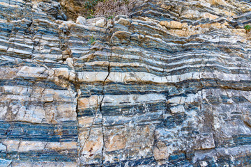 Compressed rock layers formation in various colors and thicknesses, on south central coast of the  Mediterranean island Crete, Greece. Nature and Geological science concept