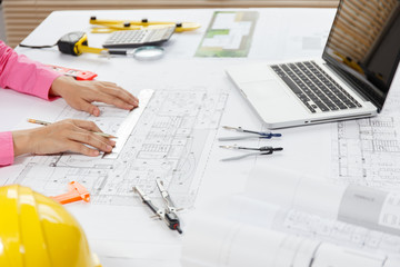 Architect hands working on blueprint plans with a pencil, a ruler, calculator, smartphone, laptop and engineering