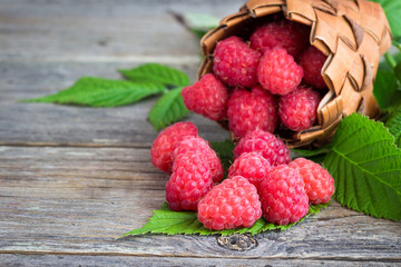 Raspberries in a basket on a wooden background.