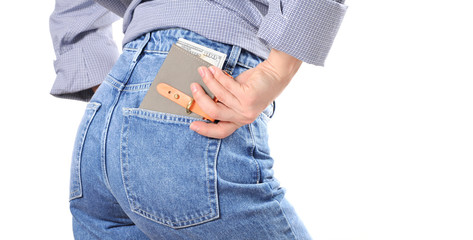 Woman's puts money in the back of jeans pocket.