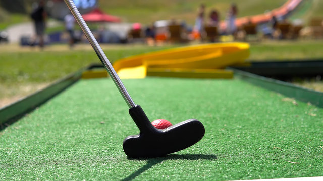 Closeup of player play mini golf with red ball