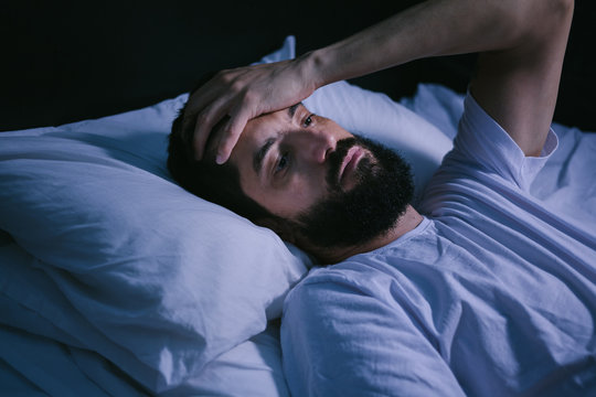 Young man in bed with eyes opened suffering insomnia and sleep disorder