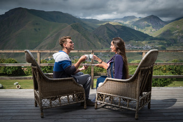 Young couple sits together on the terrace with cups of coffee in the morning. Man sends air kiss to girlfriend. Travelers having breakfast with beautiful view.
