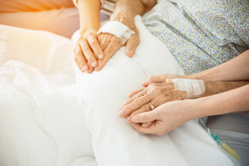 Daughter and nurse holding senior female patient's hands