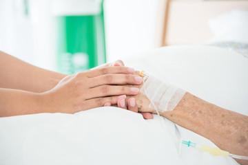 Nurse holding senior female patient hand in hospital