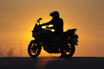 silhouette of rider on a motorbike admiring sunset - space for your text