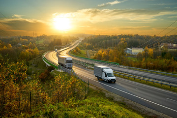 Fotobehang - Delivery van and truck driving on the highway winding through forested landscape in autumn colors at sunset