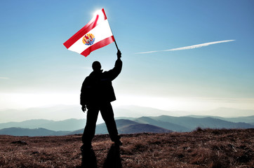 Successful silhouette man winner waving French Polynesia flag on top of the mountain peak